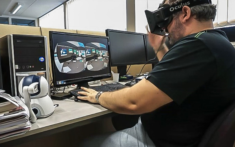 A man utilising a Virtual Reality headset at a computer