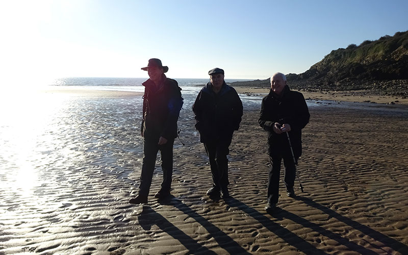 3 men happily strolling along the beach