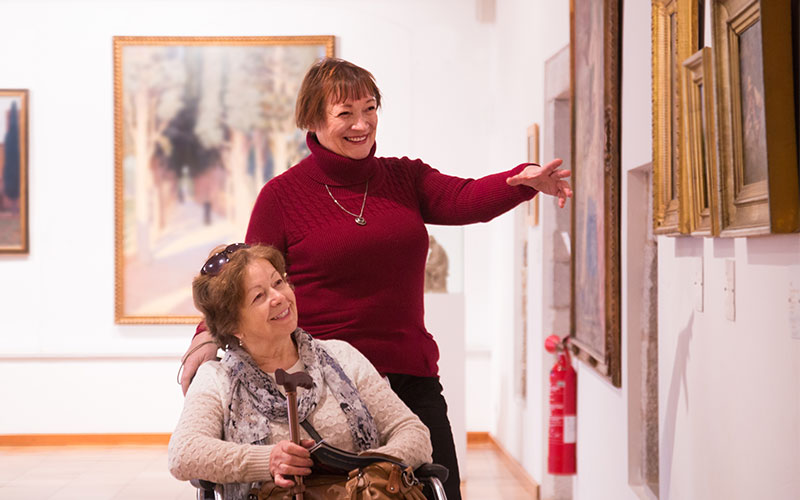 A lady in a wheelchair, along with another lady admiring the art in a gallery