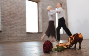 A rose and a pair of heels in the foreground with a couple dancing in the background
