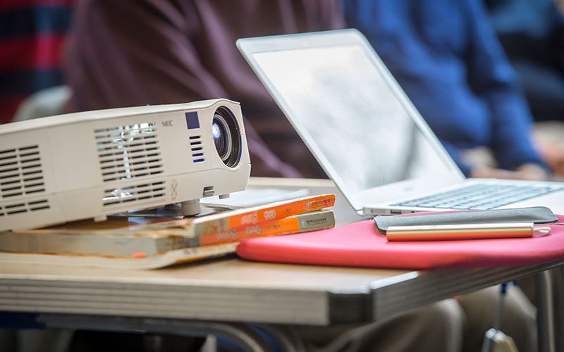 A projector resting on a desk next to a laptop