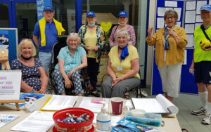 group of people wearing yellow and blue in front of a stall with a u3a poster