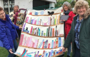 four women holding a quilt that shows a bookcase with a cat perching on the top shelf